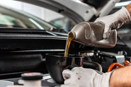 partial view of mechanic pouring motor oil at car engine