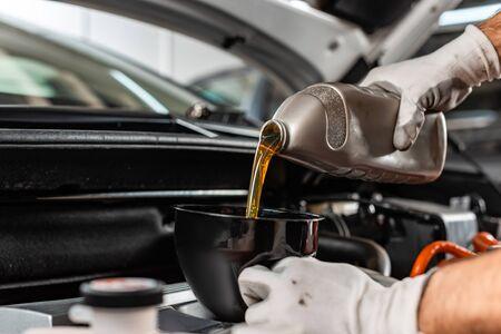Vista parcial del mecánico vertiendo aceite de motor en el motor del automóvil