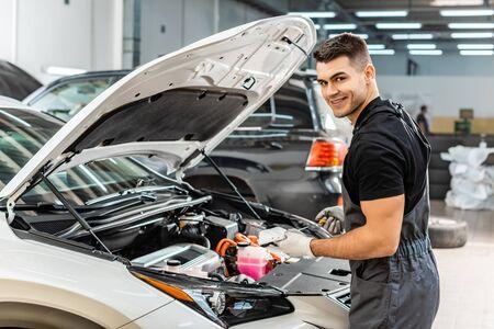 Gut aussehender Mechaniker, der Ölmessstab hält und in die Kamera lächelt Standard-Bild