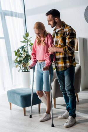 handsome bearded man standing with injured woman holding crutches at home Banque d'images