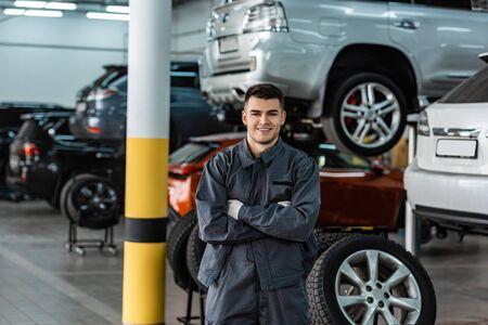 uśmiechnięty mechanik patrzący na kamerę stojąc w warsztacie ze skrzyżowanymi rękami