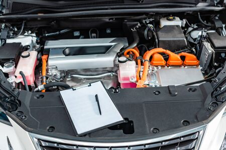 clipboard with blank white paper and pen near car engine compartment