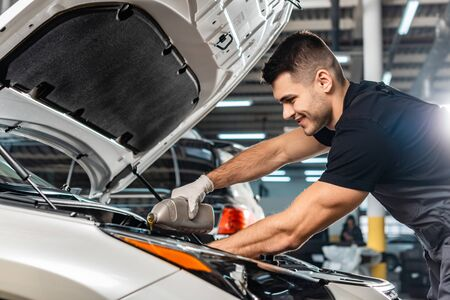 smiling mechanic pouring motor oil at car engine