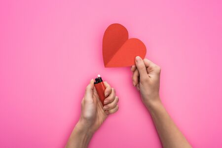 cropped view of woman lighting up empty red paper heart with lighter isolated on pink Stock Photo