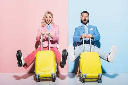 shocked woman and handsome man holding travel bags on pink and blue background