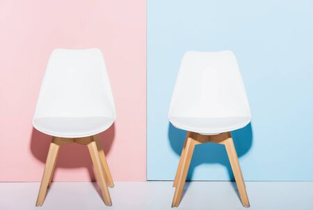 wooden and white chairs on pink and blue background