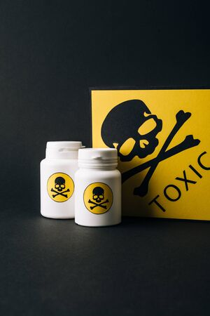 Jars and card with toxic sign isolated on black