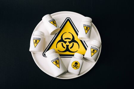 Top view of bottles with poison sign on plate with biohazard symbol isolated on black 写真素材