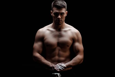 sexy muscular bodybuilder with bare torso with talcum powder on hands isolated on black
