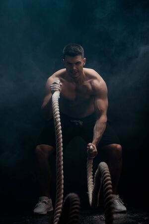 muscular bodybuilder with torso excising with battle rope on black background with smoke