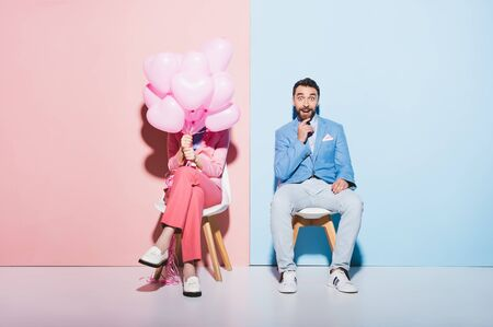 woman holding balloons and shocked man on pink and blue background