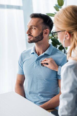 selective focus of doctor in glasses examining handsome man Stock fotó