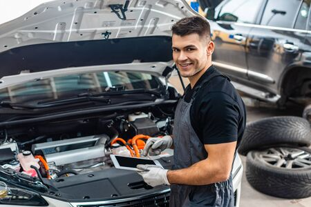 handsome mechanic smiling at camera while using digital tablet near car engine compartment