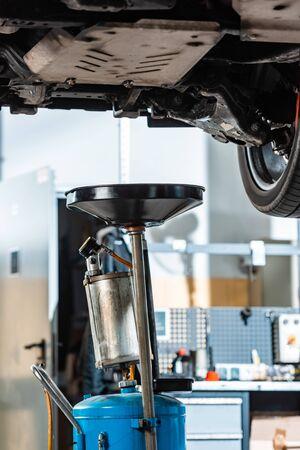 pneumatic waste oil extractor under raised car in workshop Imagens