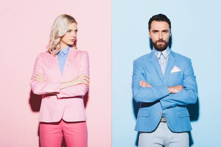 sad woman and handsome man with crossed arms on pink and blue background 版權商用圖片