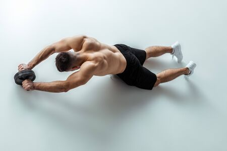 overhead view of sexy muscular bodybuilder with bare torso exercising with ab wheel on grey background