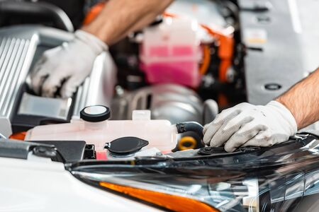 cropped view of mechanic inspecting car engine compartment 免版税图像 - 137244143