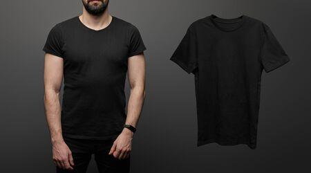 cropped view of bearded man near blank basic black t-shirt on black background