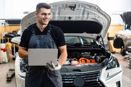 handsome mechanic holding laptop while standing near car with open hood
