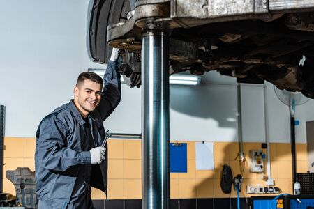 smiling mechanic holding wrench and looking at camera while standing under car raised on car lift