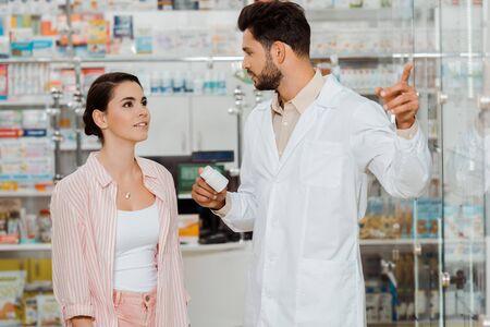 Apotheker, der ein Glas mit Pillen hält und auf die Vitrine zum Kunden zeigt