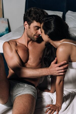handsome man in underwear embracing sexy woman in bed Banque d'images