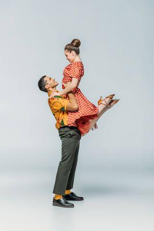 Seitenansicht des gutaussehenden Tänzers, der Partner beim Tanzen von Boogie-Woogie auf grauem Hintergrund hält
