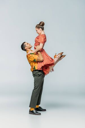 Vista lateral del guapo bailarín sosteniendo pareja mientras baila boogie-woogie sobre fondo gris