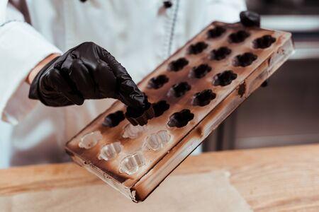 vista ritagliata del cioccolatiere che tiene caramelle al cioccolato vicino al vassoio del ghiaccio