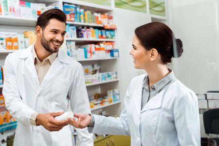 Glimlachende apotheker die aan collega-pot geeft met pillen in de apotheek