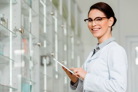 Attractive pharmacist smiling at camera while using digital tablet