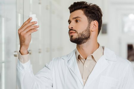 Farmacéutico en bata blanca mirando frasco con pastillas en farmacia