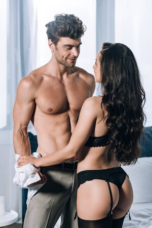 smiling, sexy man looking at sexy girl in black lingerie