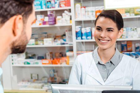 Enfoque selectivo del farmacéutico sonriendo al cliente en el mostrador de la farmacia