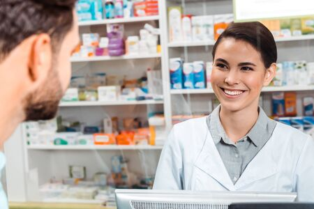 Mise au point sélective du pharmacien souriant au client au comptoir de la pharmacie