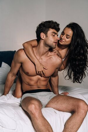 smiling, sensual girl embracing sexy, shirtless boyfriend in bedroom