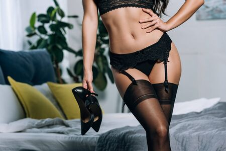 cropped view of sexy girl in black lingerie and stockings holding high heeled shoes while standing with hand on hip Stock Photo
