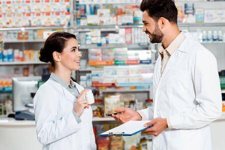 Vista lateral de farmacéuticos con pastillas y portapapeles sonriendo el uno al otro en farmacia