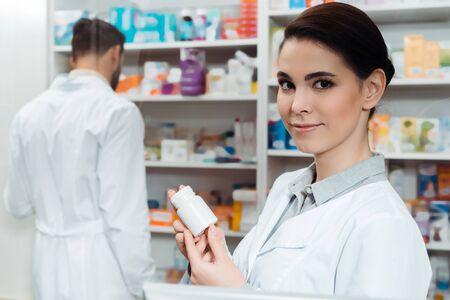 Apotheker die een pot pillen vasthoudt terwijl hij naar de camera kijkt met een collega op de achtergrond Stockfoto