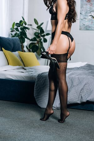 cropped view of sexy girl in black lingerie and stockings holding high heeled shoes while standing in bedroom
