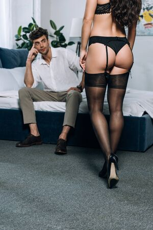 partial view of sexy girl in black lingerie and high heeled shoes near man sitting on bed in formal wear Standard-Bild - 137760065