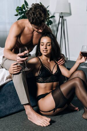 sexy woman in black lingerie and stocking sitting on floor near boyfriend while holding glasses of red wine Standard-Bild - 137760087