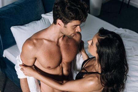 high angle view of seductive girl taking off shirt from sexy boyfriend Standard-Bild - 137760146