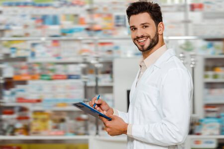 Selective focus of smiling pharmacist with clipboard looking at camera in apothecary Foto de archivo
