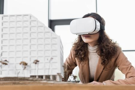 virtual reality architect in virtual reality headset looking at model of house