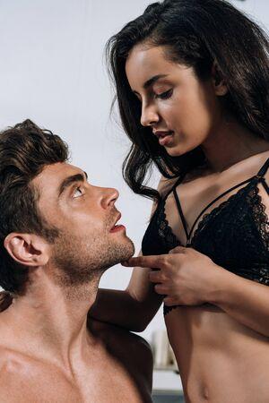 seductive young woman in black bra touching chin of sexy man Standard-Bild - 137760236