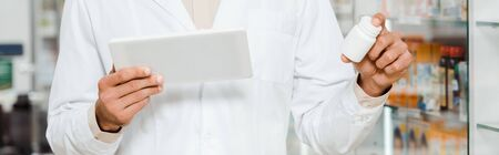 Cropped view of druggist holding digital tablet and jar with pills, panoramic shot