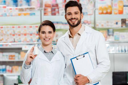 Farmacéutico sonriente con portapapeles y frasco de pastillas mirando a cámara en farmacia