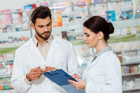 Apothekers in witte jassen met pillen en klembord door drogisterijshowcase Stockfoto