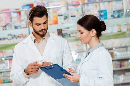Pharmacists in white coats with pills and clipboard by drugstore showcase Stockfoto